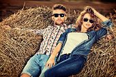 image of haystacks  - Romantic young couple in casual clothes sitting together in haystack - JPG