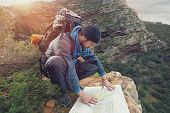 foto of wilder  - Lost hiker with backpack checks map to find directions in wilderness area - JPG