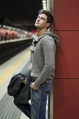 Handsome Young Man Standing Against Wall In Train Or Subway Station