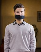 stock photo of gag  - Young man with gag  - JPG