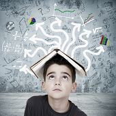 stock photo of academia  - boy with book on his head overwhelmed by the chaos of the subjects - JPG