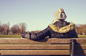 picture of breather  - woman resting on a park bench looking at the distance deep in thought - JPG
