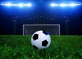 Постер, плакат: Soccer ball on the penalty point in a stadium at night