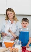 stock photo of flour sifter  - Portrait of mother and son making cookies at kitchen counter - JPG