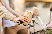 summer holidays, bikes, love, relationship and dating concept - closeup of woman hand holding coffee