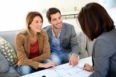stock photo of draft  - Couple meeting architect for house construction - JPG