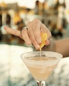 picture of bartender  - Female bartender is squeezing orange juice into a cocktail glass - JPG