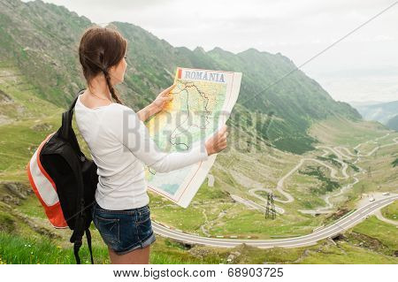 Girl tourist in mountain read the map.