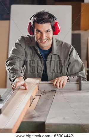 Portrait of confident carpenter cutting wooden plank with tablesaw in workshop