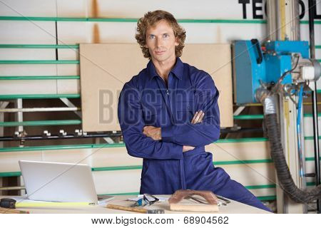 Portrait of confident carpenter standing with arms crossed against vertical panel saw