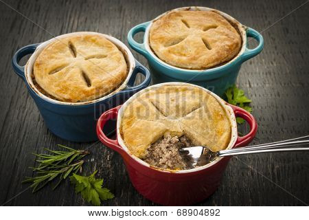 Three homemade gourmet meat pies with fork in ground beef filling on rustic wood background