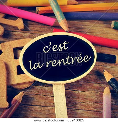 the sentence c'est la rentree, back to school written in french in a blackboard label, on a wooden table and colored pencils of different colors