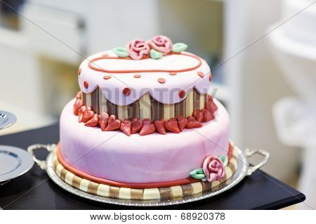 Wedding Cake Decorated With Pink Rose Flowers And Hearts .