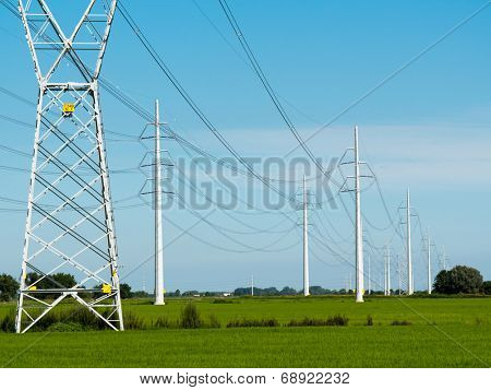 High voltage power lines, green fields, sunny summer day.
