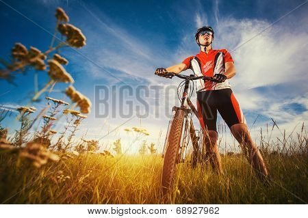 man is riding bicycle outside in the field