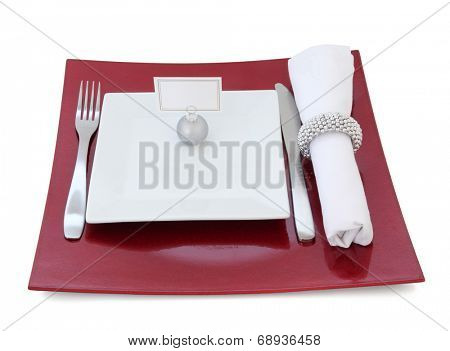 Christmas dinner place setting with plate, cutlery, name tag on bauble and serviette with silver napkin ring over white background.
