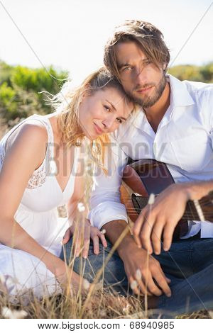 Handsome man serenading his girlfriend with guitar smiling at camera on a sunny day