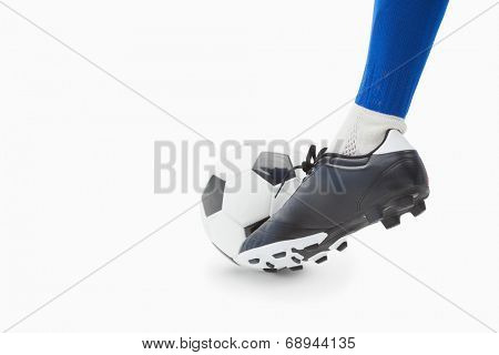 Football player in blue controlling the ball on white background