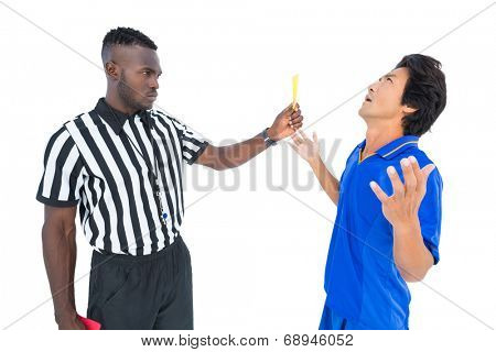 Serious referee showing yellow card to player on white background