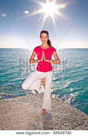 Beautiful yong woman practicing yoga on seashore at sunset