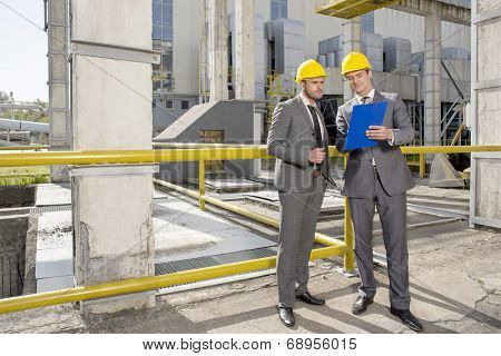 Full length of young male architects looking at clipboard on construction site