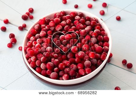 Frozen Cranberries in Bowl within heart shaped cookie cutter