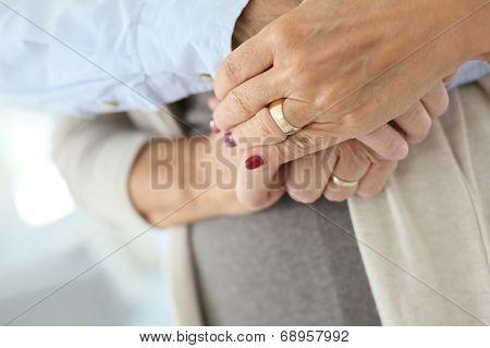Closeup of senior people's hands held togehter