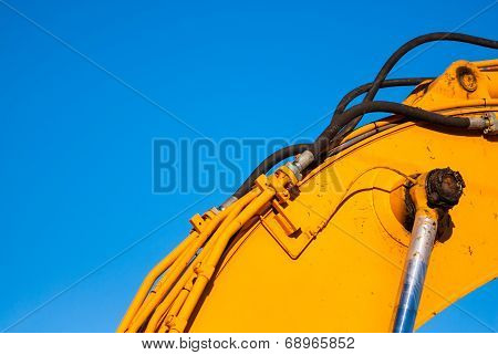 Yellow Machinery And Hydraulics On Blue Sky.