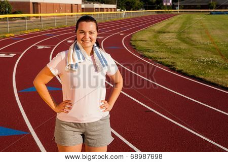 Young Woman Exercising On A Track Outdoors