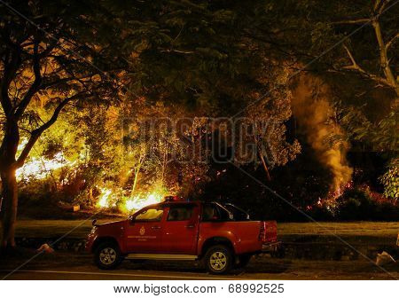 PUCHONG, MALAYSIA - JULY 26, 2014: A forest fire blazes onto the foot hills of the Air Hitam Forest Reserve in Puchong, Malaysia.  The recent dry season makes the forest susceptible to forrest fires.