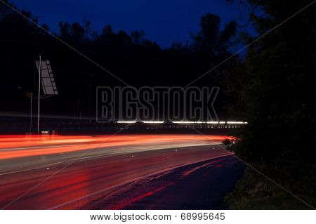 Red Tail Light Trails On Curve Road