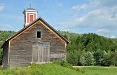 image of cupola  - Old weathered wooden barn with a red cupola in a field in Vermont - JPG