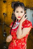 foto of traditional attire  - Chinese girl in traditional Chinese cheongsam blessing - JPG