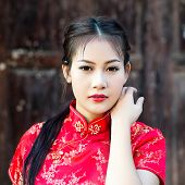 image of traditional attire  - Chinese girl in traditional Chinese cheongsam blessing - JPG
