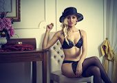 picture of tease  - fashion shot of sexy blond woman with hat and black lingerie posing and sitting in elegant indoor - JPG