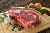 pic of rib eye steak  - Raw meat ready to be cooked on wooden background  - JPG