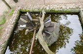 stock photo of water-mill  - stylized small wooden water mill on the stone base of the park pond
