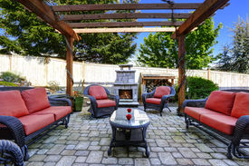 picture of grass area  - Backyard cozy patio area with wicker furniture set and brick fireplace - JPG