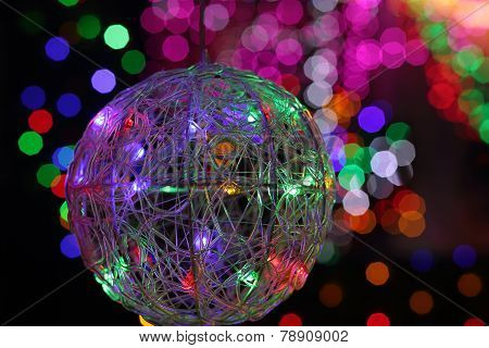 Christmas Wire Mesh Bauble And Coloured Backgound Of Defocused Lights