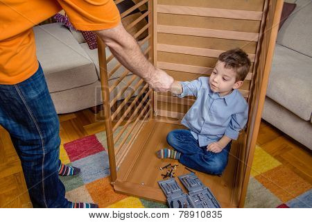 Son and father assembling cot for a newborn at home