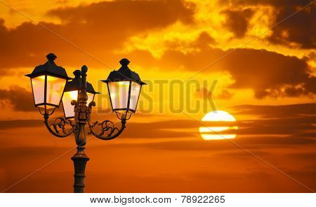 Orange Sky With A Shining Sun And A Lamppost