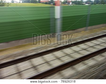 tracks and rails out in motion from a moving train. symbolic photo for train, tempo and dynamics.
