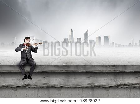 Young man in suit sitting on building and playing violin
