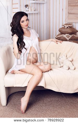 Pregnant Woman With Long Dark Hair Posing In Cozy Interior