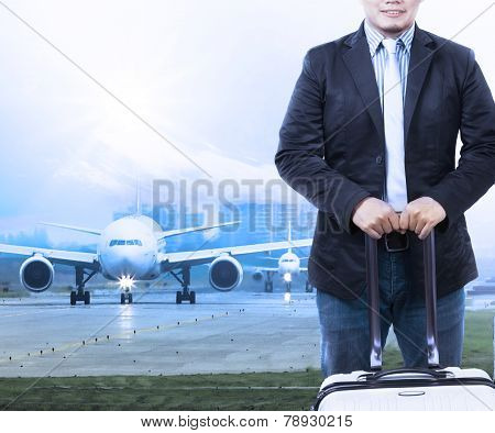 Young Man And Traveling Luggage Staning In Front Of Air Plane Taxi On Airport Runways Preparing To F