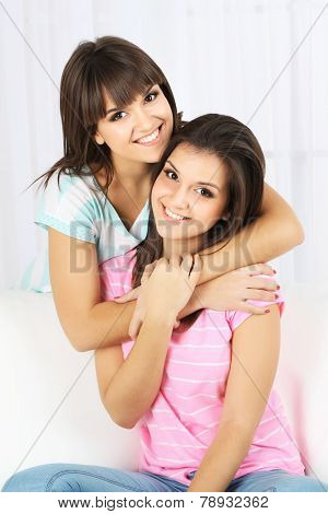 Beautiful girls twins sitting on sofa in room