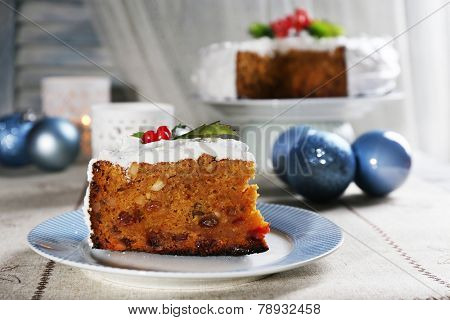 Slice of cake on plate with Christmas decoration on wooden background