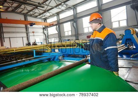 industrial worker operating metal sheet profiling mechine at manufacturing factory
