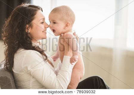 Happy mother playing with a small child.