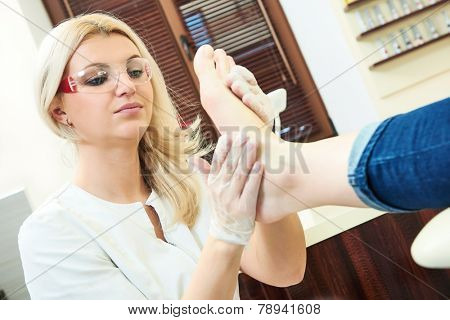 Pedicure nail technician worker perfoming procedure for foot care in beauty salon